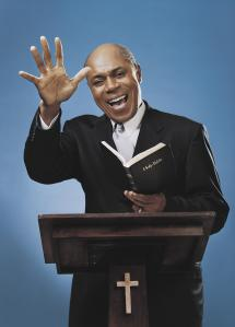Man Stands at a Podium Preaching From a Bible With One Arm Raised