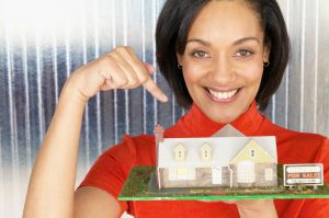 Woman Pointing to Model Home for Sale
