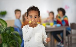Multiracial small boy with group of children eating snack and looking at camera indoors at nursery school.